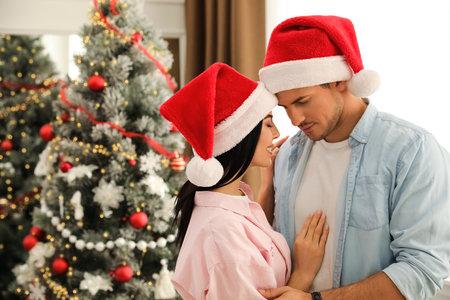 Happy couple in Santa hats near Christmas tree at home