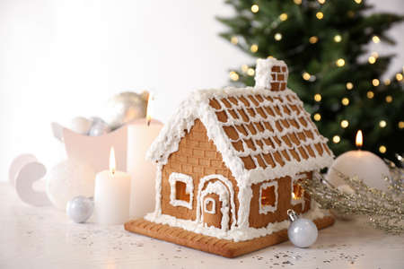 Beautiful gingerbread house decorated with icing and candles on white table Standard-Bild