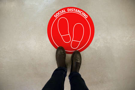 Keep social distance as preventive measure during coronavirus outbreak. Red warning sign on floor in front of man, closeup