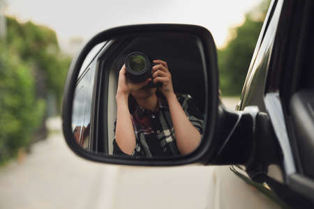 Private detective with camera spying from auto, view through car side mirror