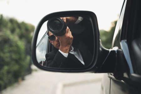 Private detective with camera spying from auto, view through car side mirror Banco de Imagens