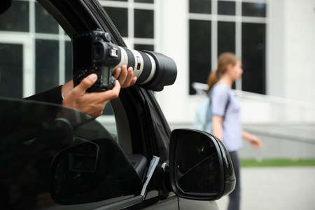 Private detective with camera spying from car, closeup
