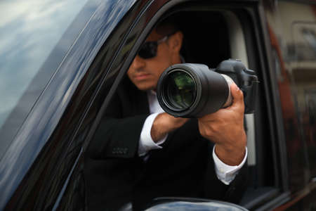 Private detective with camera spying from car, focus on lens Imagens