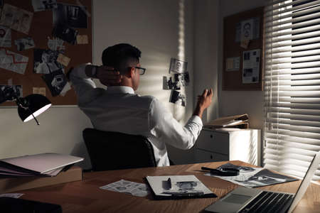 Detective looking at evidence board in office
