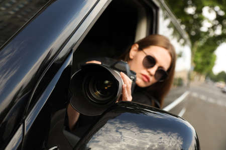 Private detective with modern camera spying from car, focus on lens