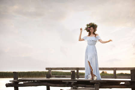 Young woman wearing wreath made of beautiful flowers on pier near river Stock fotó