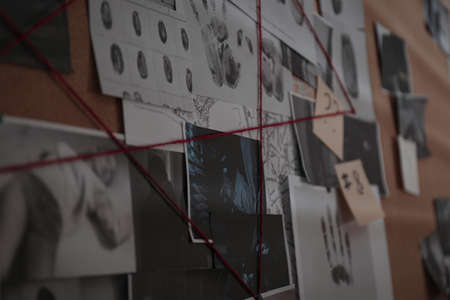 Detective board with crime scene photos, stickers, clues and red thread, closeup