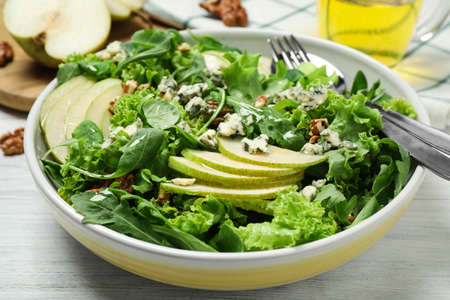 Fresh salad with pear on white wooden table, closeup