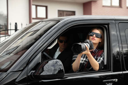 Private detectives with modern camera spying from car Imagens