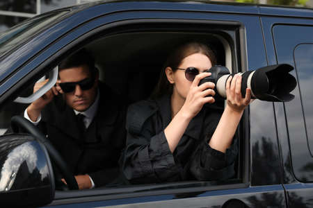 Private detectives with modern camera spying from car Banco de Imagens