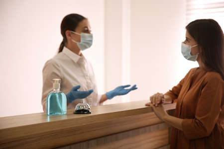 Receptionist with client at countertop in hotel, focus on dispenser bottle of antiseptic gel and service bell