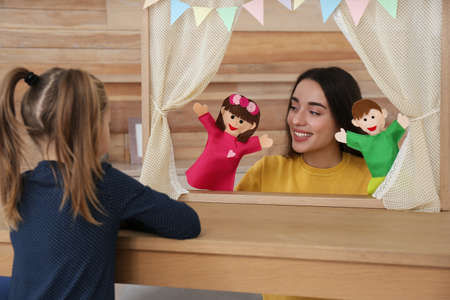 Mother puppet show for her daughter performing at home Banco de Imagens