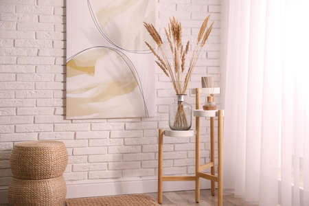 Fluffy reed plumes and painting in stylish room interior