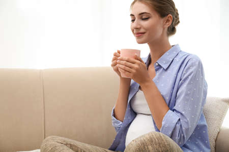 Happy pregnant woman drinking tea at home