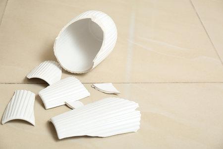 Broken white ceramic vase on floor. Space for text