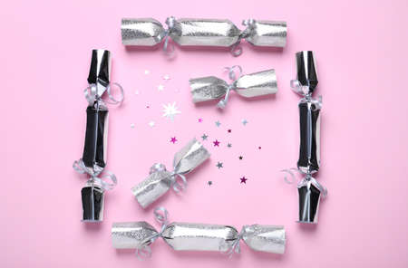 Silver Christmas crackers and shiny confetti on pink background, flat lay