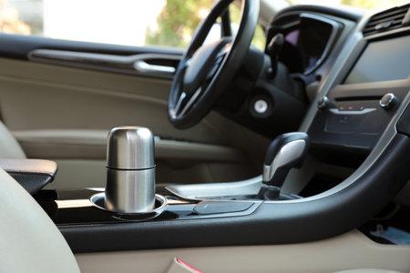 Silver flask in holder inside of car Foto de archivo