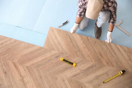 Worker installing laminated wooden floor indoors, above view