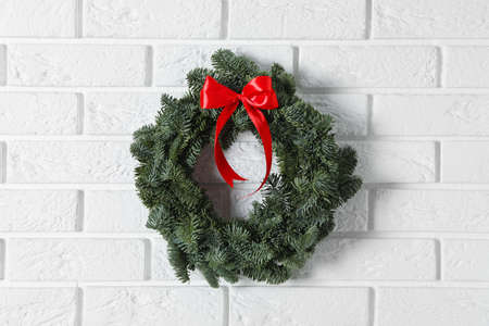 Christmas wreath made of fir tree branches with red ribbon on white brick wall