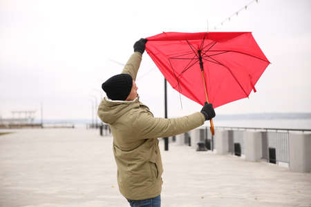 Man with red umbrella caught in gust of wind outdoors