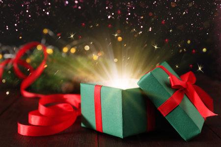 Beautiful Christmas gift box with magic light on table