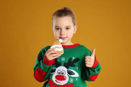Cute little girl with Christmas gingerbread cookie on orange background