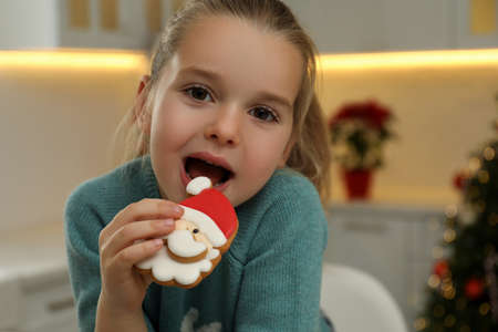 Cute little girl with Christmas gingerbread cookie at home
