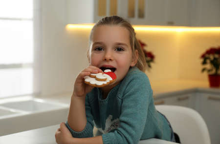 Cute little girl with Christmas gingerbread cookie at table indoors