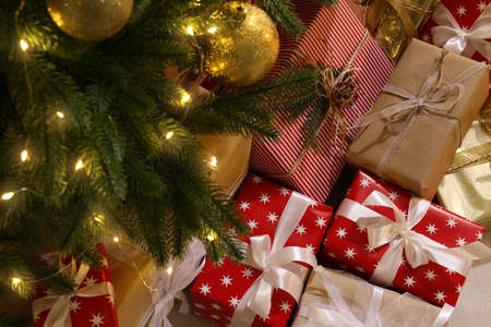 Gift boxes under Christmas tree with fairy lights
