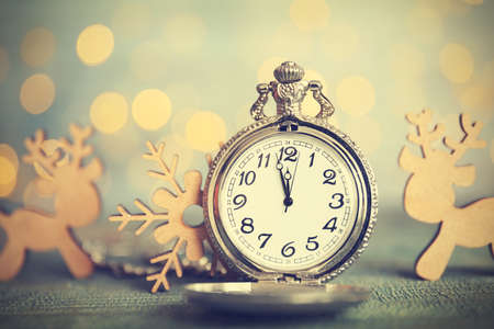Pocket watch and festive decor on table against blurred lights. New year countdown