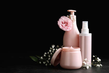Set of hair cosmetic products and flowers on stone table against black background. Space for text