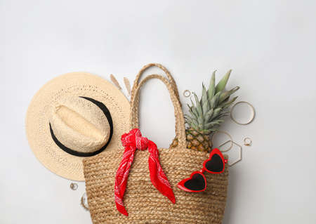 Stylish straw bag and summer accessories on white background, flat lay Banque d'images
