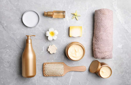 Flat lay composition with hair cosmetic products on gray marble table