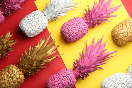 Many white, pink and golden pineapples on color background, flat lay. Creative concept