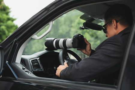 Private detective with camera spying from car