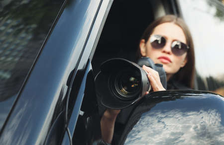 Private detective with camera spying from car, focus on lens