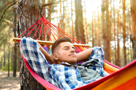 Man resting in hammock outdoors on summer day