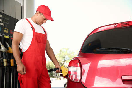 Worker refueling car at modern gas station