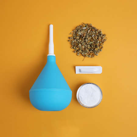 Enema, suppository, dry chamomile and bowl of salt on yellow background, flat lay