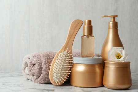 Different hair products, towel and brush on white marble table