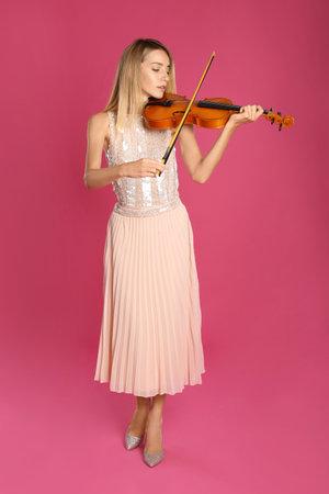 Beautiful woman playing violin on pink background Standard-Bild