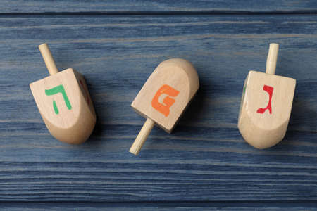 Hanukkah traditional dreidels with letters He, Pe and Gimel on blue wooden table, flat lay Reklamní fotografie