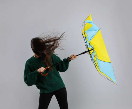 Woman with umbrella caught in gust of wind on gray background Banco de Imagens