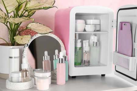 Cosmetics refrigerator and skin care products on table Foto de archivo