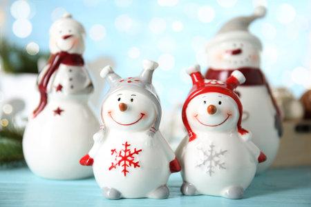 Four decorative snowmen on light blue table