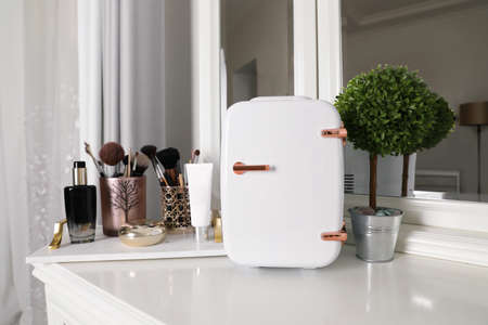 Mini fridge for cosmetic products on white vanity table