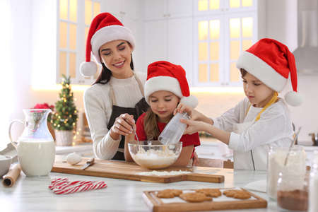 Mother with her cute little children making Christmas cookies in kitchen