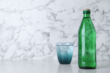 Glass and bottle with water on table against white marble background, space for text