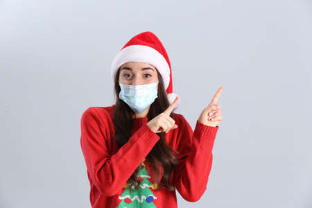 Beautiful woman wearing Santa Claus hat and medical mask on light gray background