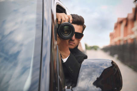 Private detective with camera spying from car Banque d'images